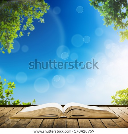 Open book on wood planks over sky with leaves background - stock photo