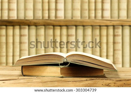 open book on wooden board and books background