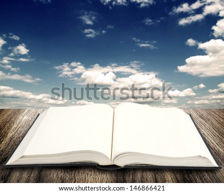 Open book on wooden planks at sky background - stock photo