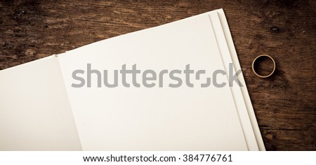 Open book on wooden surface with blank white page. One wedding ring on the side. Empty space for copy. Conceptual image of divorce.
