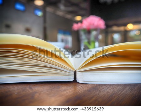 Open book on wooden table and blurred coffee shop background