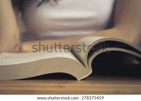 Open book on wooden table closeup. Back blurred the background you can see a girl reading a book. Vintage processing. - stock photo