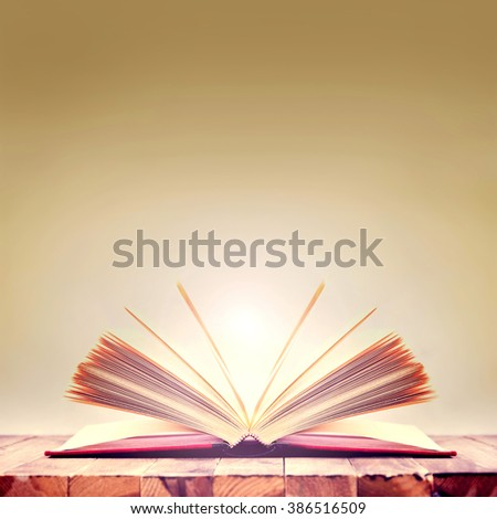 Open book on wooden table. Knowledge and education conceptual image.