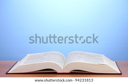 Open book on wooden table on blue background - stock photo