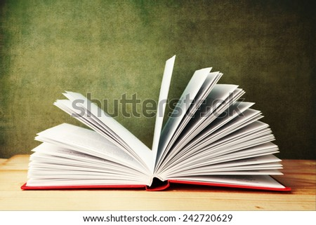 open book on wooden table on textured vintage background - stock photo