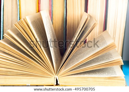 Open book, stack of colorful hardback books isolated on white background. Back to school. Copy space for text. Toned image.