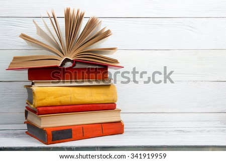 Open book, stack of colorful hardback books on wooden table. Back to school. Copy space for text - stock photo