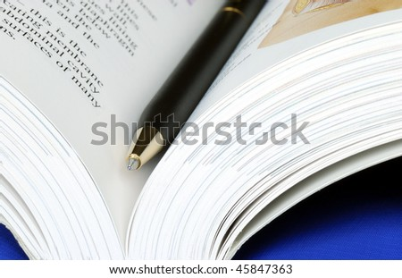 Open book with a pen isolated on blue - stock photo
