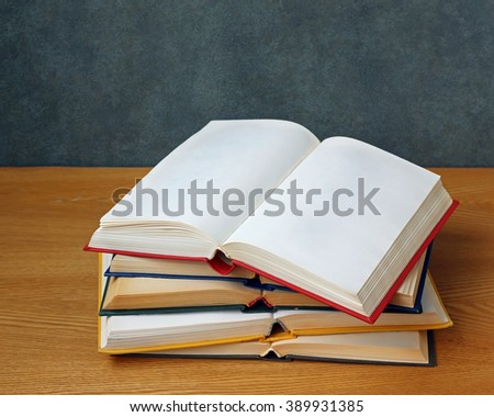 Open book with blank pages on a stack of other books on the table. - stock photo
