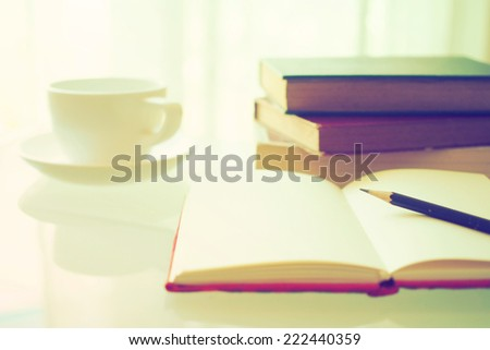 open book with cup of coffee in vintage light tone color - stock photo
