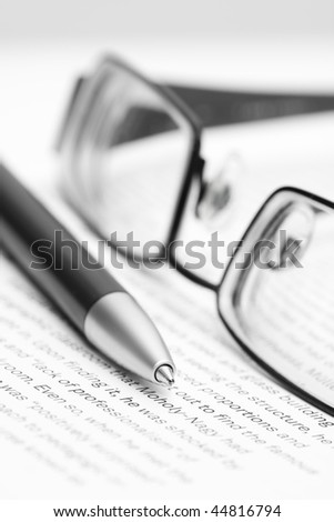 Open book with eyeglasses and pen in black and white