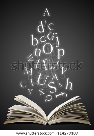 Open book with falling letters over black background - stock photo