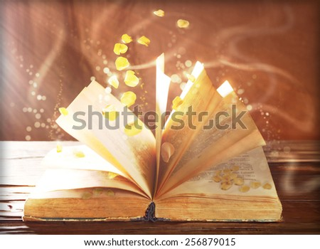 Open book with flying petals on table on brown background - stock photo