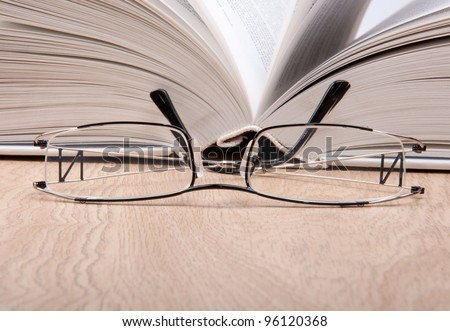 open book with glasses - stock photo