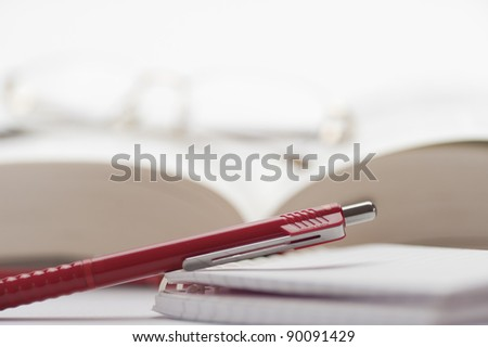 Open book with glasses and a pen to take notes - stock photo