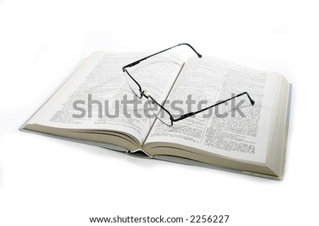Open book with glasses on it isolated on white - stock photo