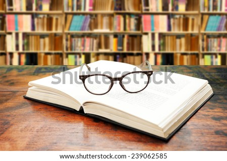Open book with glasses on the desk against library  - stock photo