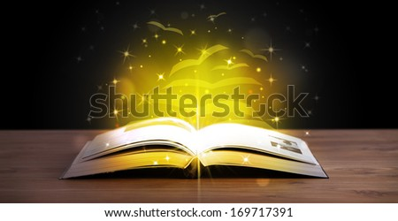 Open book with golden glow flying paper pages on wooden deck - stock photo