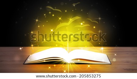 Open book with golden glow flying paper pages on wooden deck