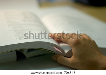 open book with hand, soft focus - stock photo