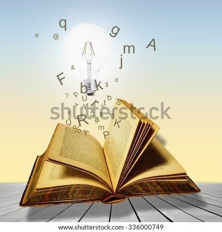 Open book with lightbulb and letters. Concept of the importance of reading. - stock photo