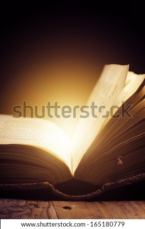 Open book with magic light - stock photo