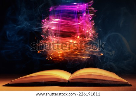 Open book with magic lights on dark background - stock photo