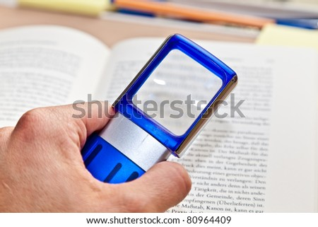 Open book with magnifying glass - stock photo