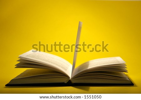 Open book with pages on yellow background - stock photo