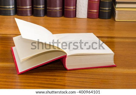 Open book with red cover on a wooden table against of the other books on the background