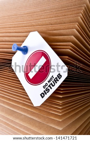 "Open book with sheets and a label with ""do not disturb"" sign. Do not disturb with my reading or learning concept shot/Do not disturb with my reading - stock photo"