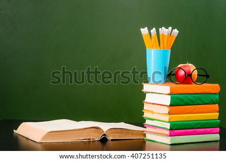 Open book with stack of books near empty green chalkboard