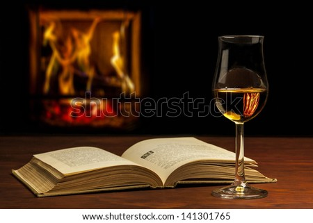 Open book with Whiskey and fire - stock photo