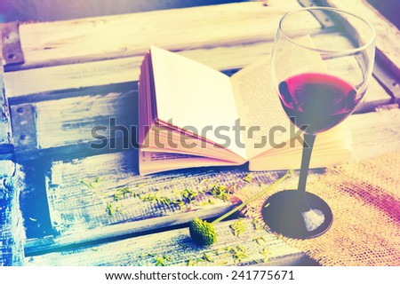 Open book with wine glass on a wooden background - stock photo
