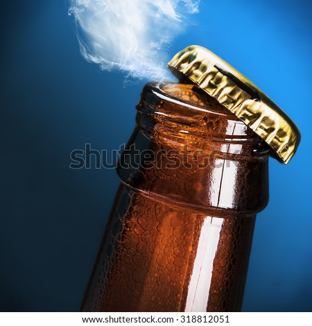 open bottle of beer on a blue background - stock photo