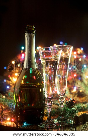 Open bottle of champagne and 2 full glasses in holiday setting. Celebration with Champagne. Christmas or New Year's holiday celebration concept. - stock photo