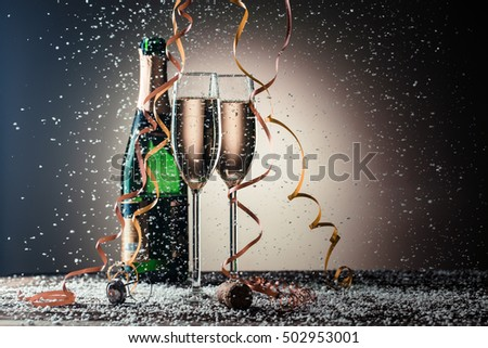 Open bottle of champagne and two filled glasses, festive composition