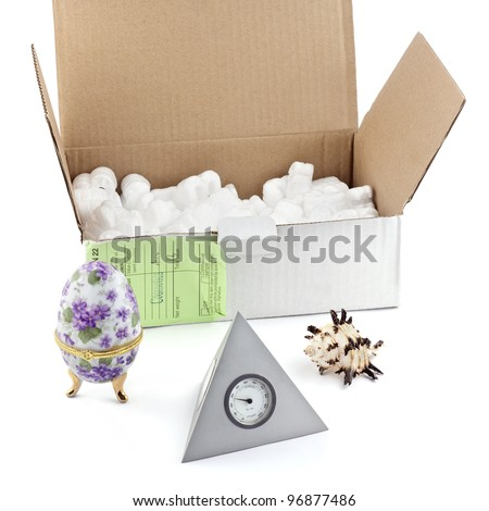 Open box with packing 'peanuts' and objects isolated on white