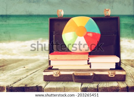 open briefcase with books and beach ball. sea in the background, filtered image. - stock photo
