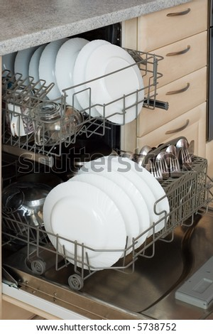 Open built-in dishwasher with set of clean dishes, plates, glasses and forks with spoons. - stock photo