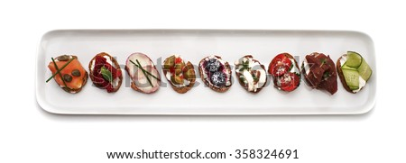 Open canape sandwiches and crostinis on a plate isolated on white. Party food crackers with different toppings. - stock photo