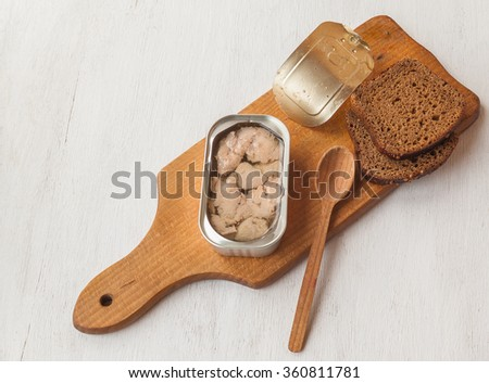 Open cans of canned liver cod and slices of rye bread on a cutting board - stock photo