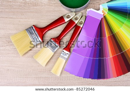Open cans with bright colors, brushes and palette on wooden background