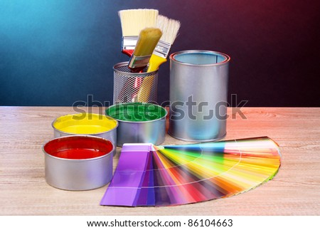 Open cans with bright colors, brushes and palette on wooden table - stock photo