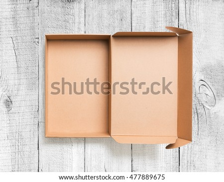 Open cardboard box top view on wooden background