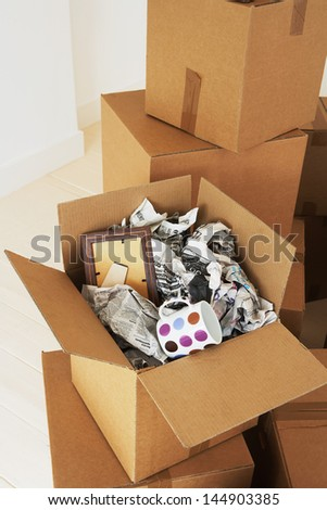 Open cardboard box with crumpled newspaper; coffee cup and frame inside - stock photo