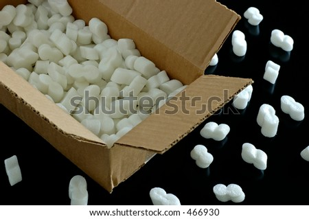 Open cardboard box with packing styrofoam peanuts inside and some spilled outside