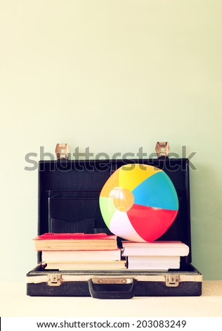 open case with books and beach ball. vacation or travel  concept. - stock photo