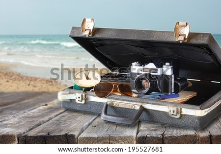open case with old camera sunglasses and clock in front of seascape. filtered image. - stock photo