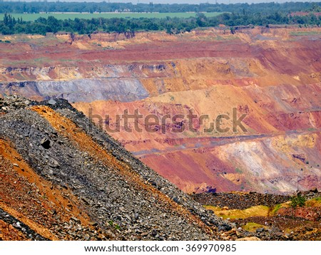 Open cast mine with natural landscape on the background and colorful ore dump on the foreground - stock photo
